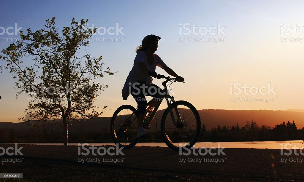 Silhouette of a girl riding a bike along a river royalty-free stock photo