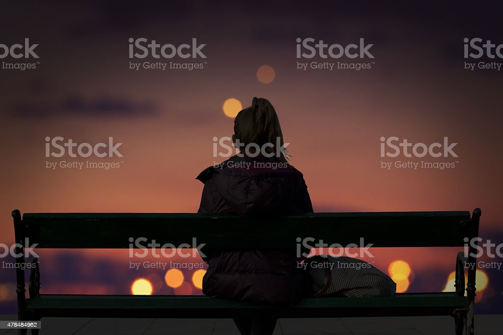 Silhouette of a girl watching defocused city lights stock photo