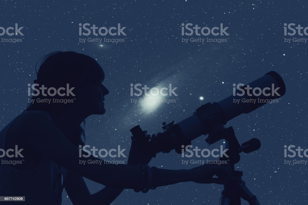 Silhouette of a girl while watching stars through the telescope.