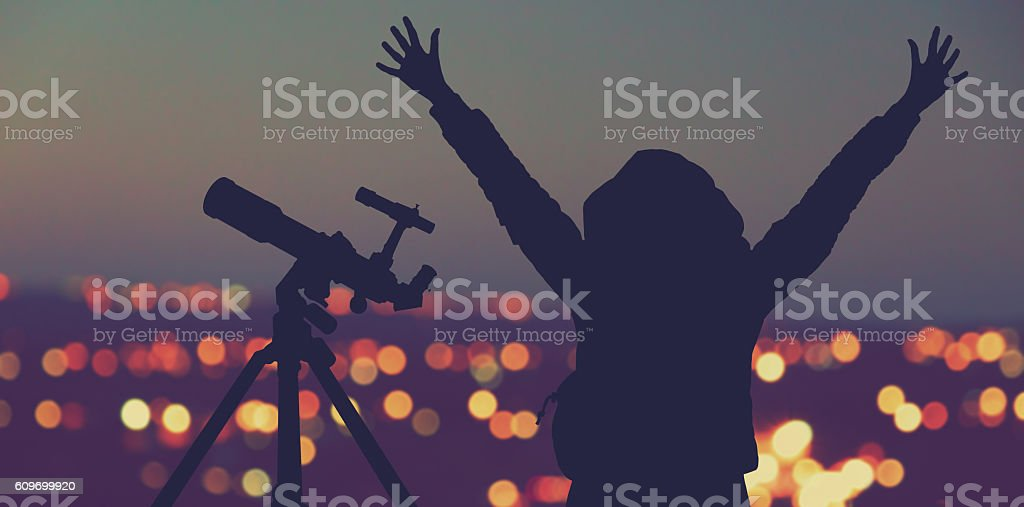 Silhouette of a girl with telescope and de-focused city lights. stock photo
