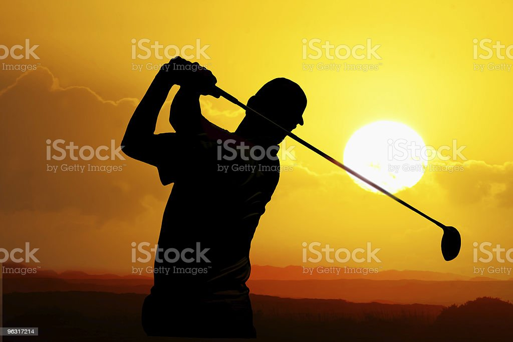 Silhouette of a golfer taking a swing at sunset royalty-free stock photo