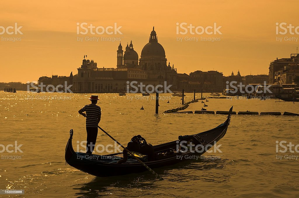 Silhouette of a gondolier rowing his boat in Venice, Italy royalty-free stock photo