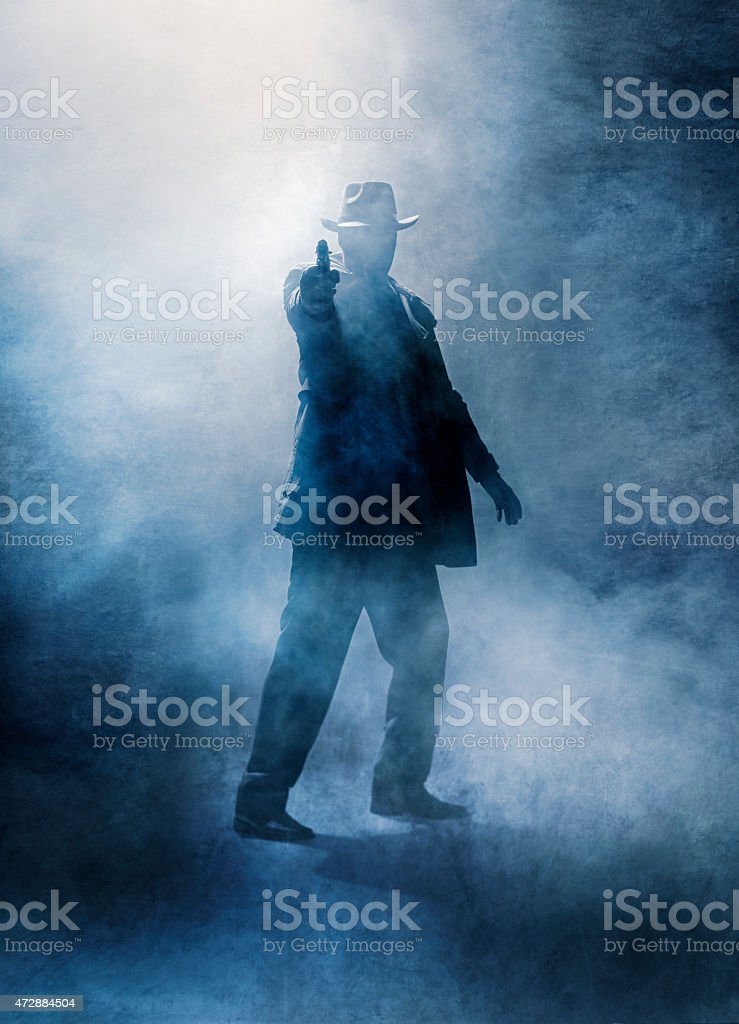 A silhouette of a gun man with a smoky background stock photo