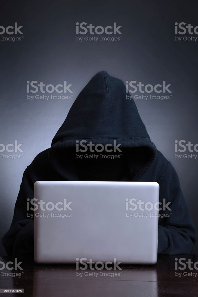 Silhouette of a hacker looking in monitor stock photo