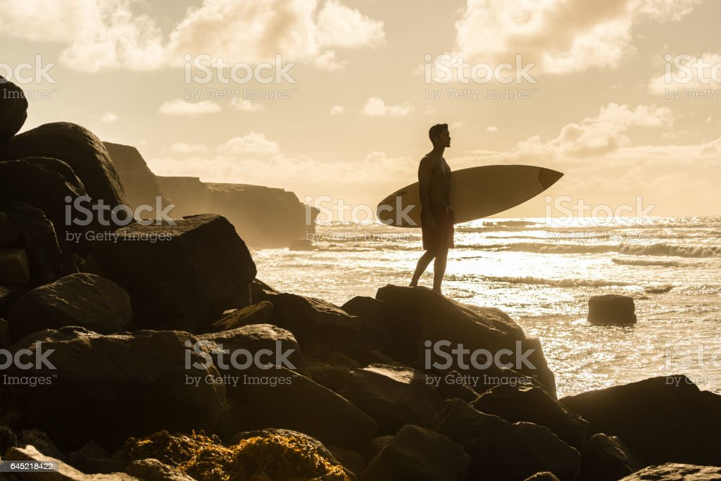 Silhouette of a Hispanic Man With His Surboard stock photo