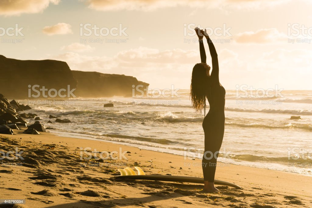 Silhouette of a Hispanic Women Stretching With Her Surboard stock photo