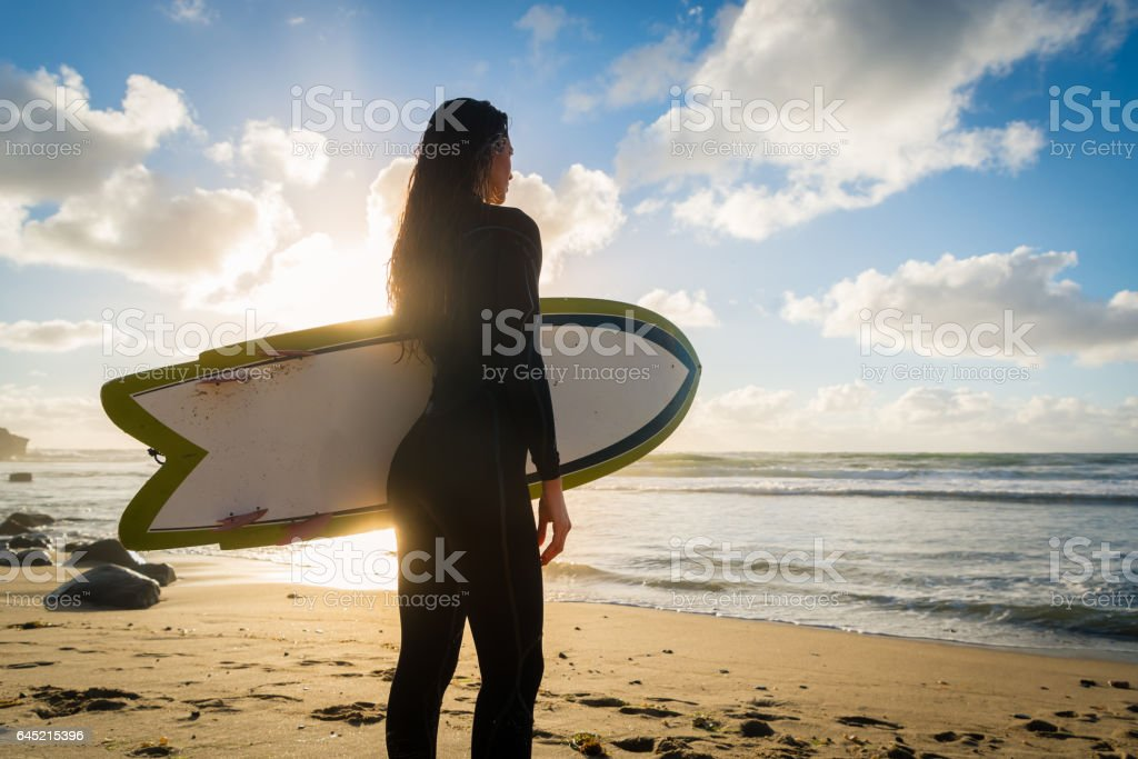 Silhouette of a Hispanic Women With Her Surboard stock photo