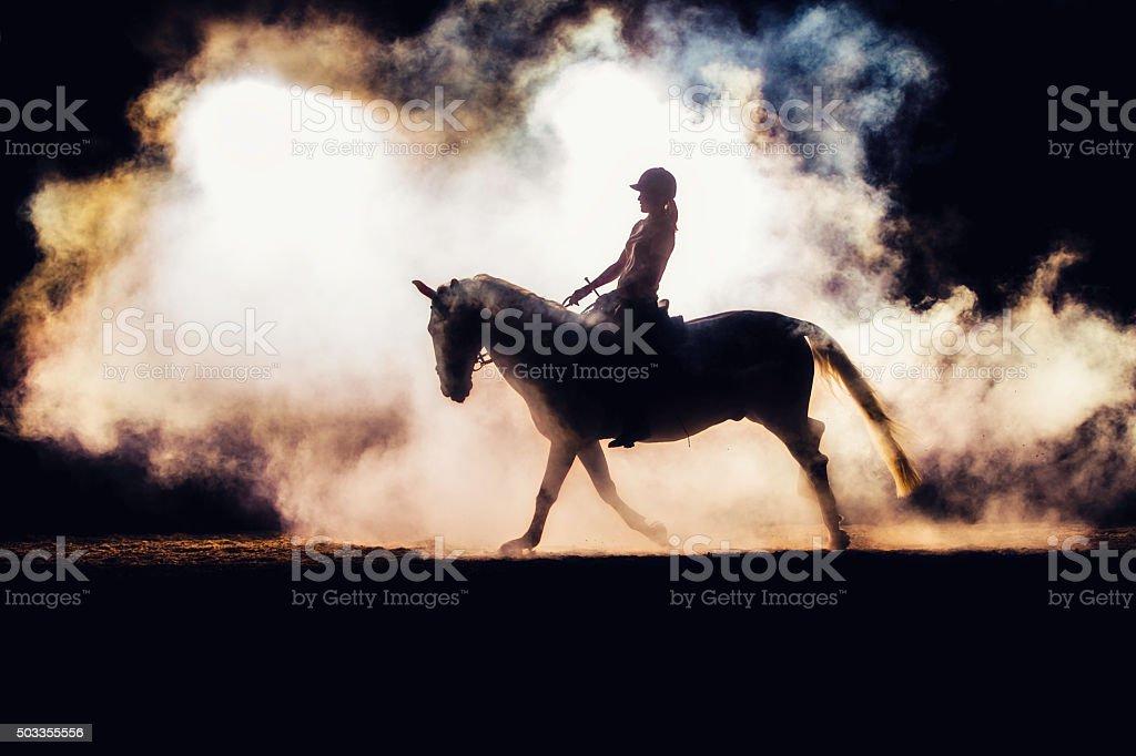 Silhouette of a horseback rider in smoke stock photo
