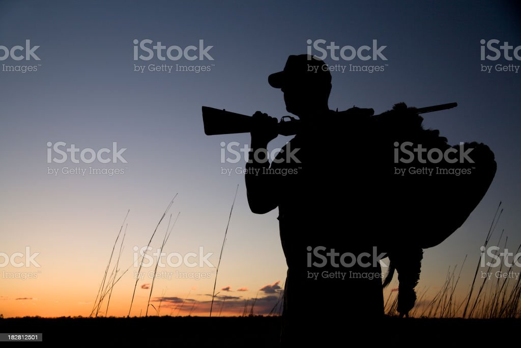 Silhouette of a hunter at sunset stock photo