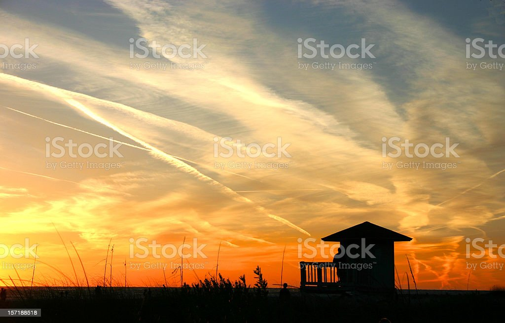Silhouette of a hut against a beach sunset stock photo