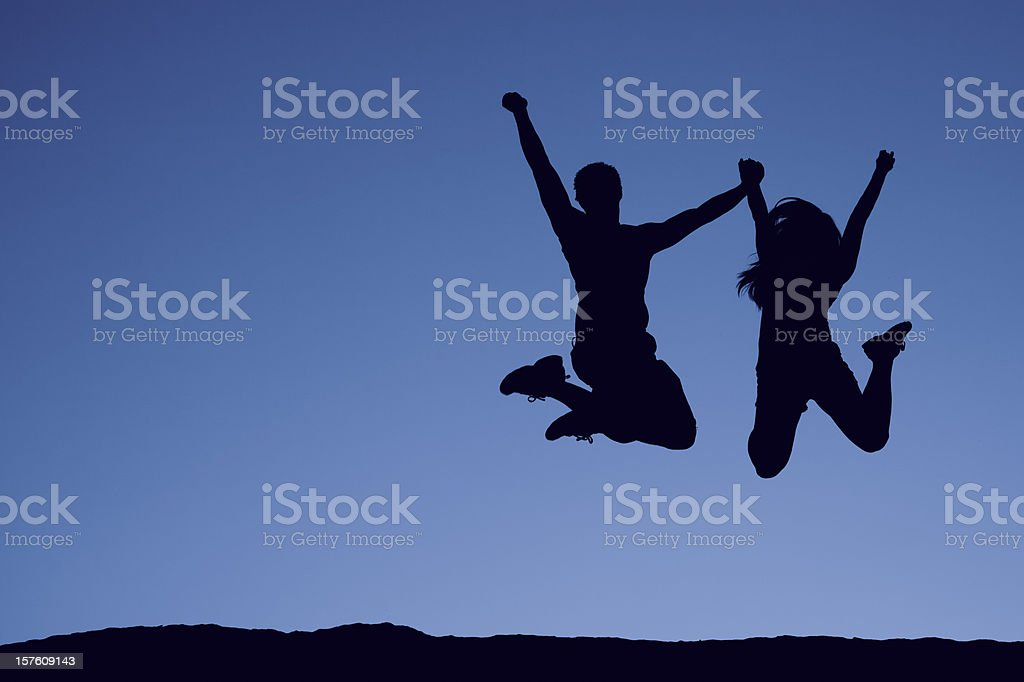Silhouette of a Jumping Couple stock photo