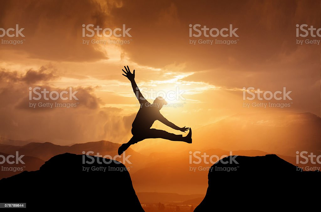 Silhouette of a jumping  man on summit stock photo