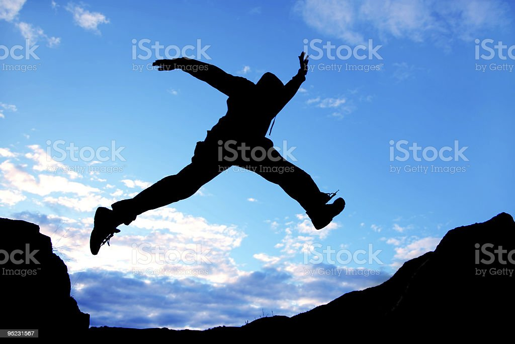 Silhouette of a jumping man under blue sky royalty-free stock photo