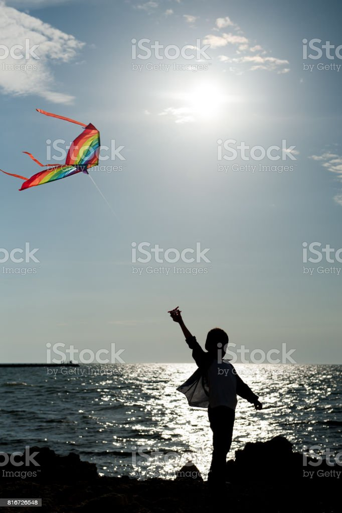 silhouette of a little boy with flying kite on the background of the sea and sky stock photo
