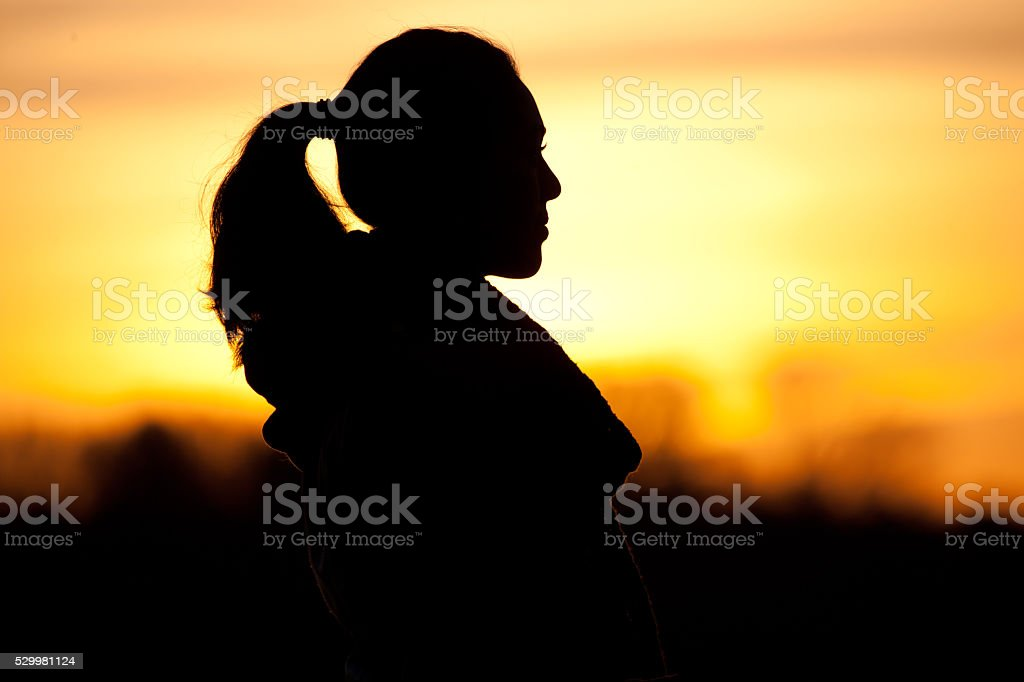 Silhouette of a long haired female at dawn stock photo