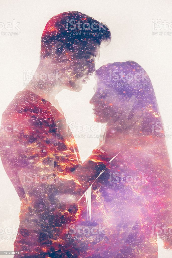 Silhouette of a loving couple with galaxy in their forms stock photo