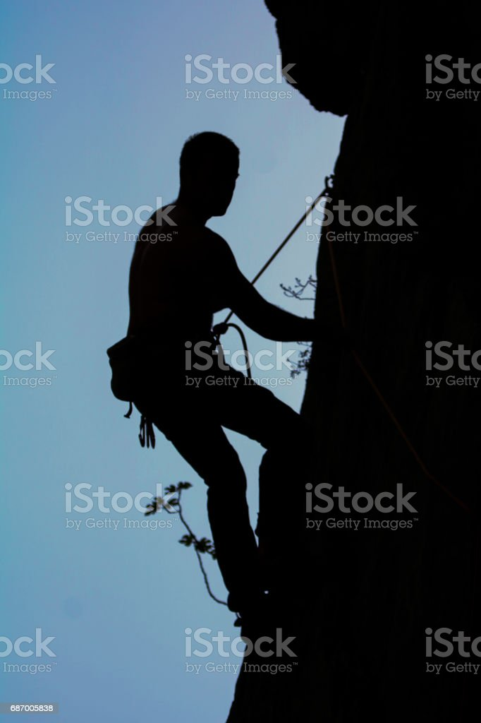 Silhouette of a male rock climber in divide and in sunset. stock photo