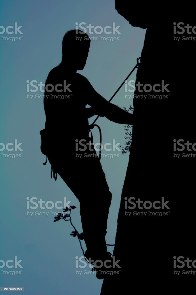 Silhouette of a male rock climber in sunset. stock photo