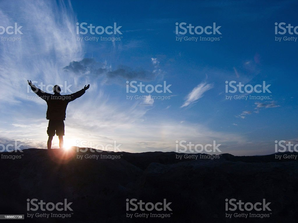 Silhouette of a man against a cloudy sky stock photo