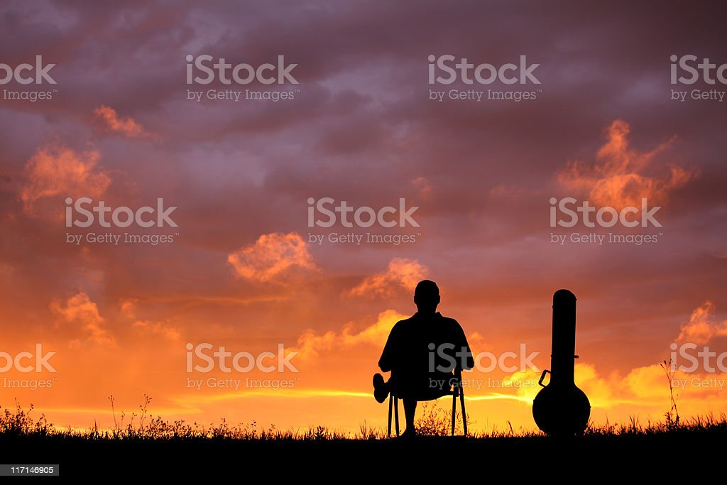 Silhouette of a Man and His Banjo stock photo