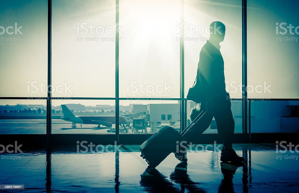 Silhouette of a man at the Airport with Suitcase stock photo