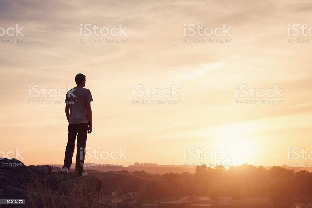 Silhouette of a man at the sunset on the mountain stock photo