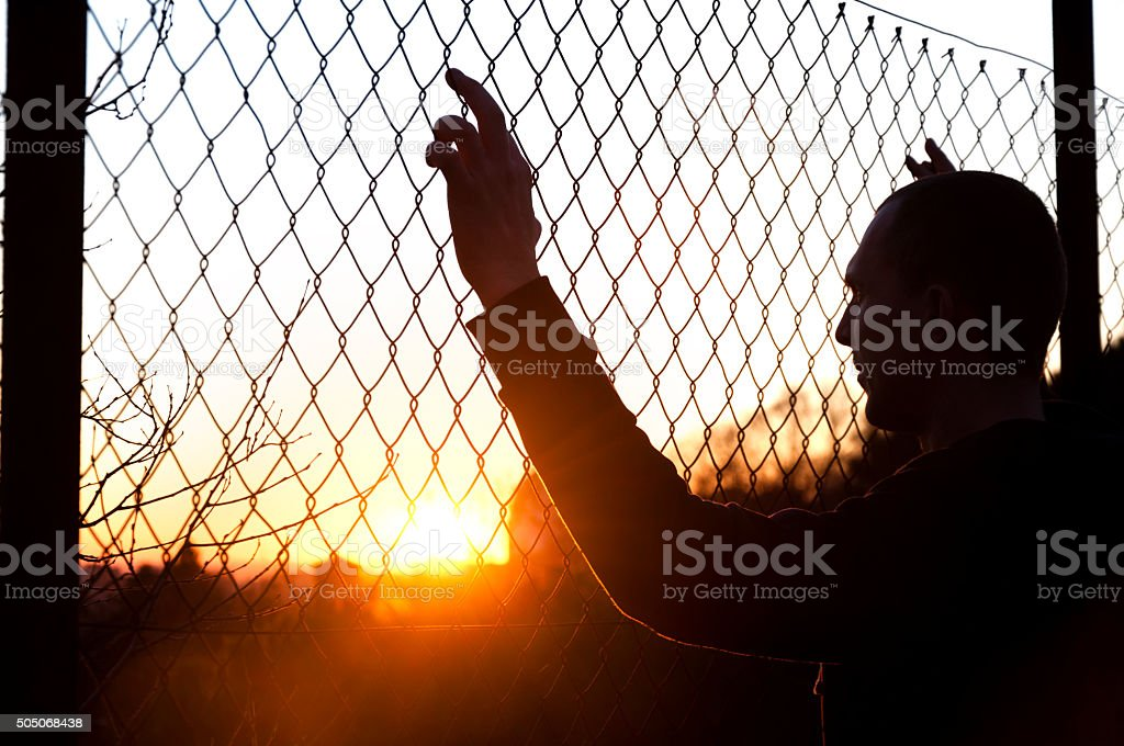 silhouette of a man behind the fence stock photo