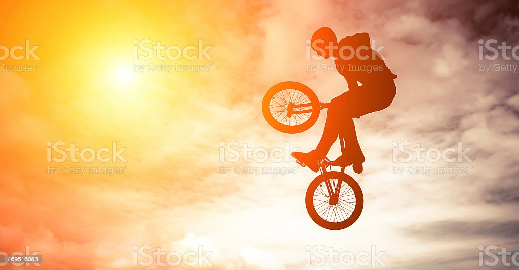 Silhouette of a man doing a jump on a bmx bike in the sky stock photo