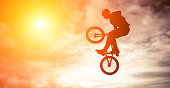 Silhouette of a man doing a jump on a bmx bike in the sky