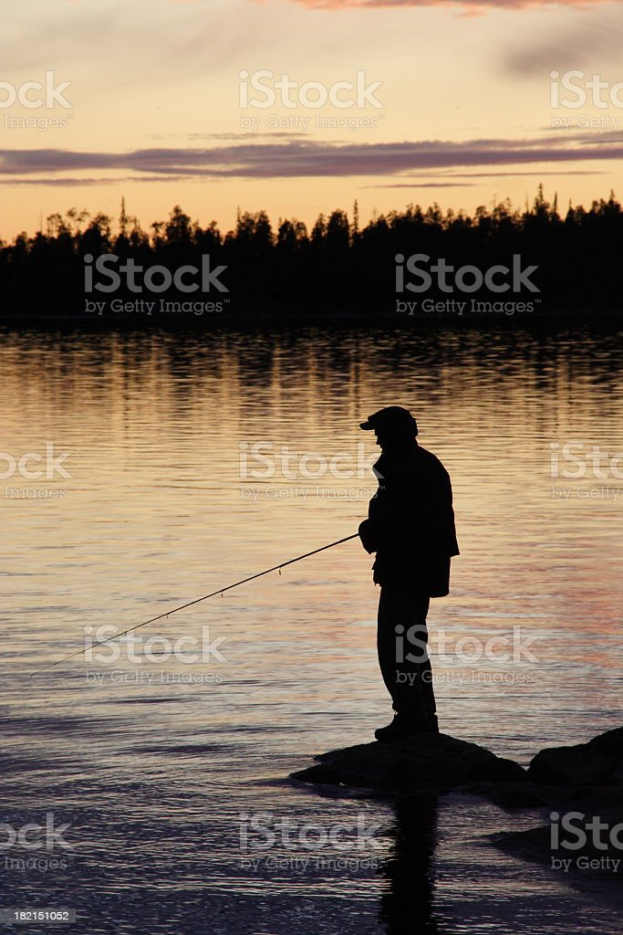 Silhouette of a man fishing at dusk stock photo