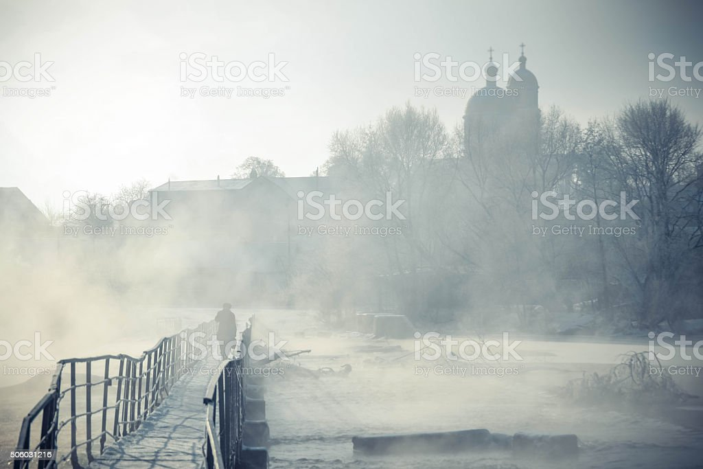 silhouette of a man goes across the bridge over  river stock photo