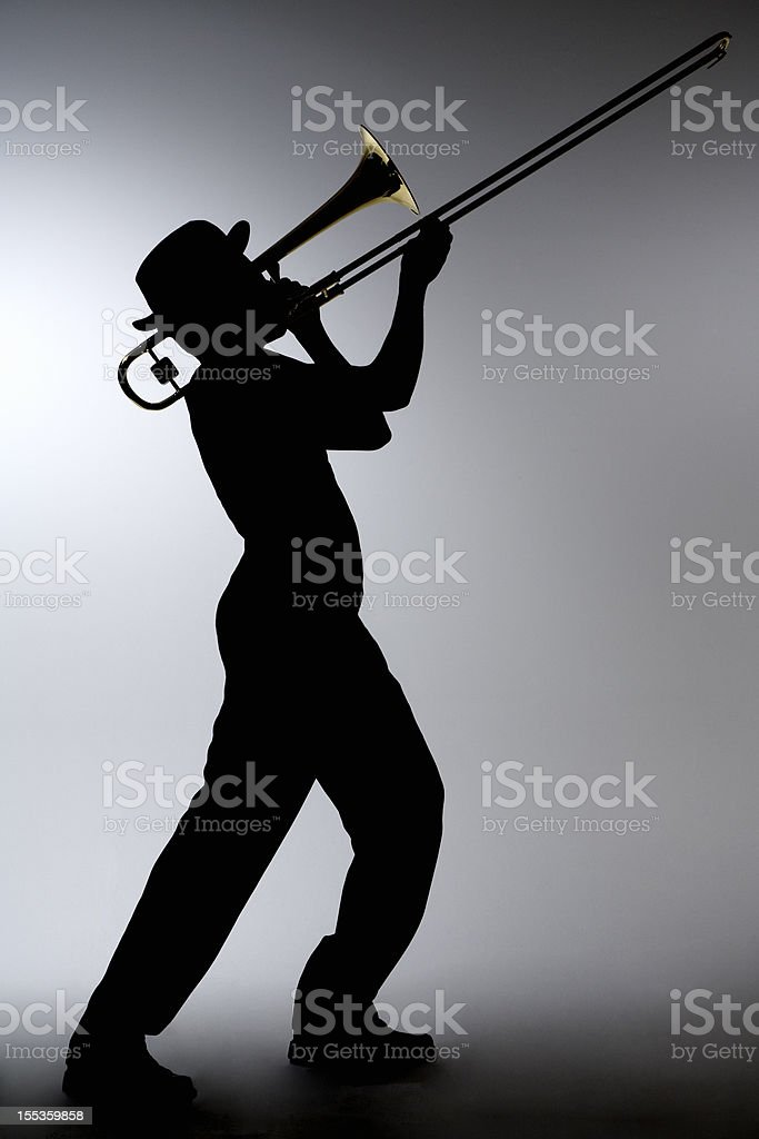 Silhouette of a man in a porkpie hat playing the trombone stock photo