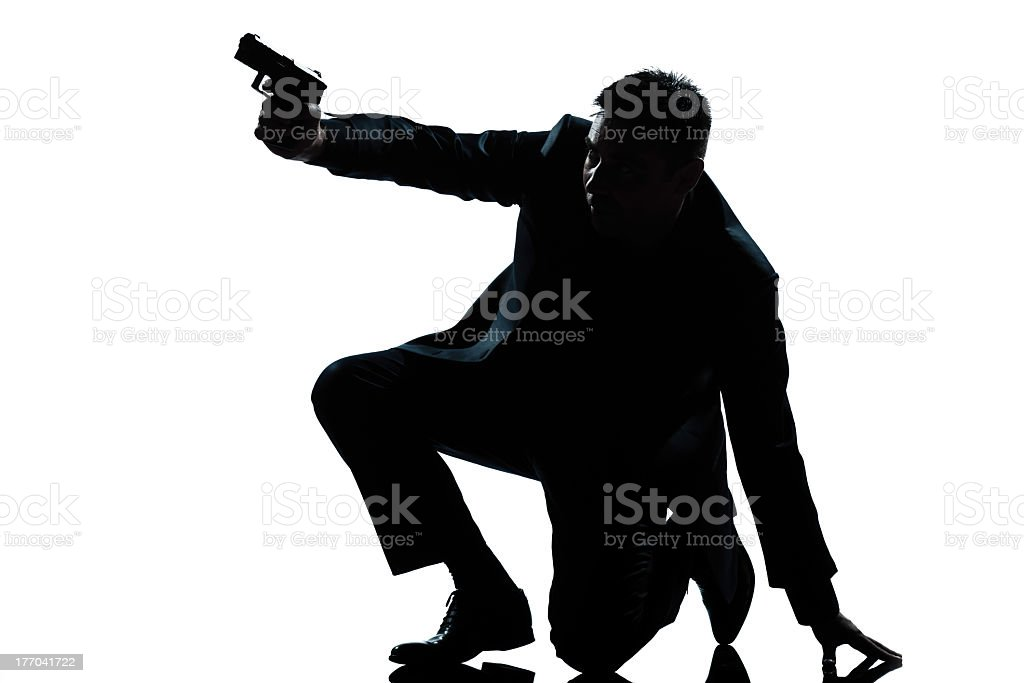 Silhouette of a man in a suit kneeling aiming a pistol stock photo