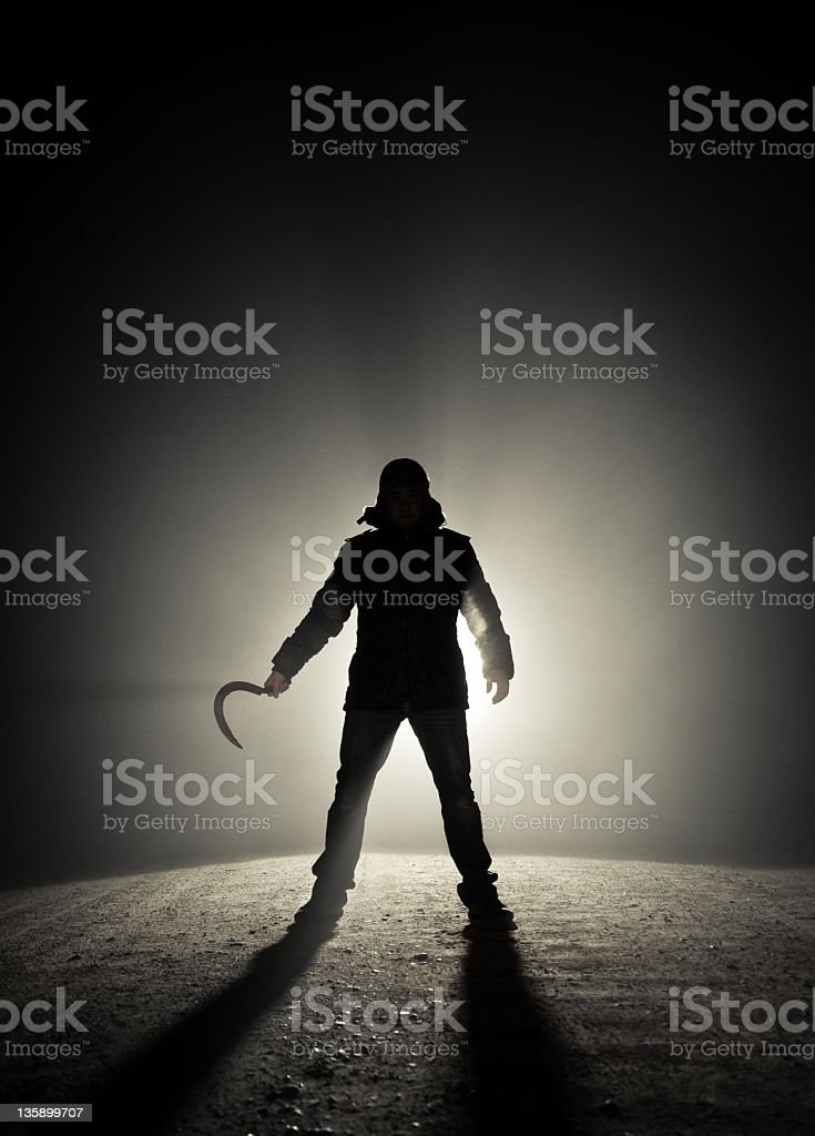 Silhouette of a man in an alley holding a sickle in his hand stock photo