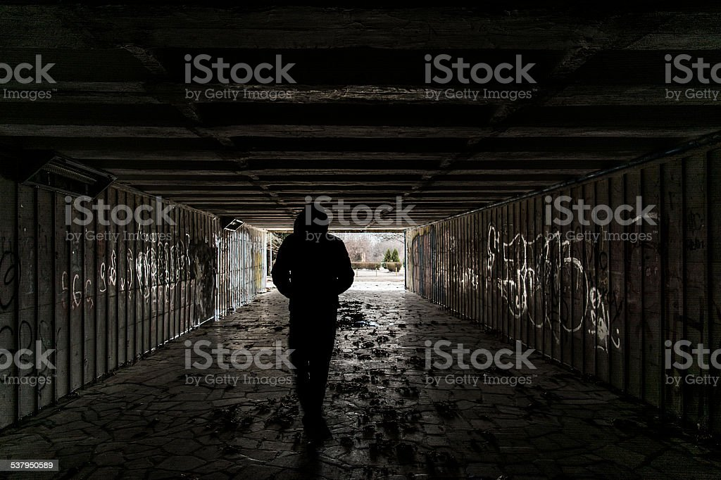 Silhouette of a man in tunnel stock photo