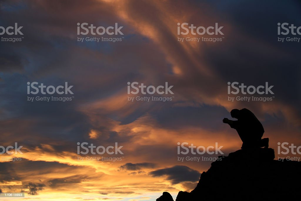 Silhouette of a Man Kneeling and Praying on Mountain stock photo