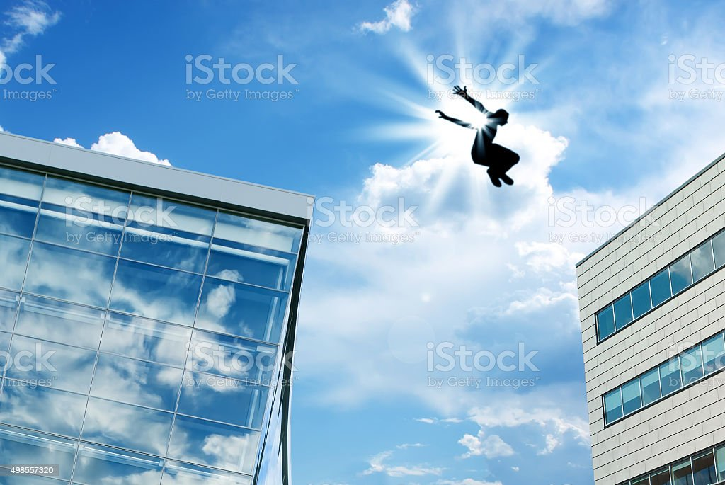Silhouette of a Man Leaping off Building stock photo