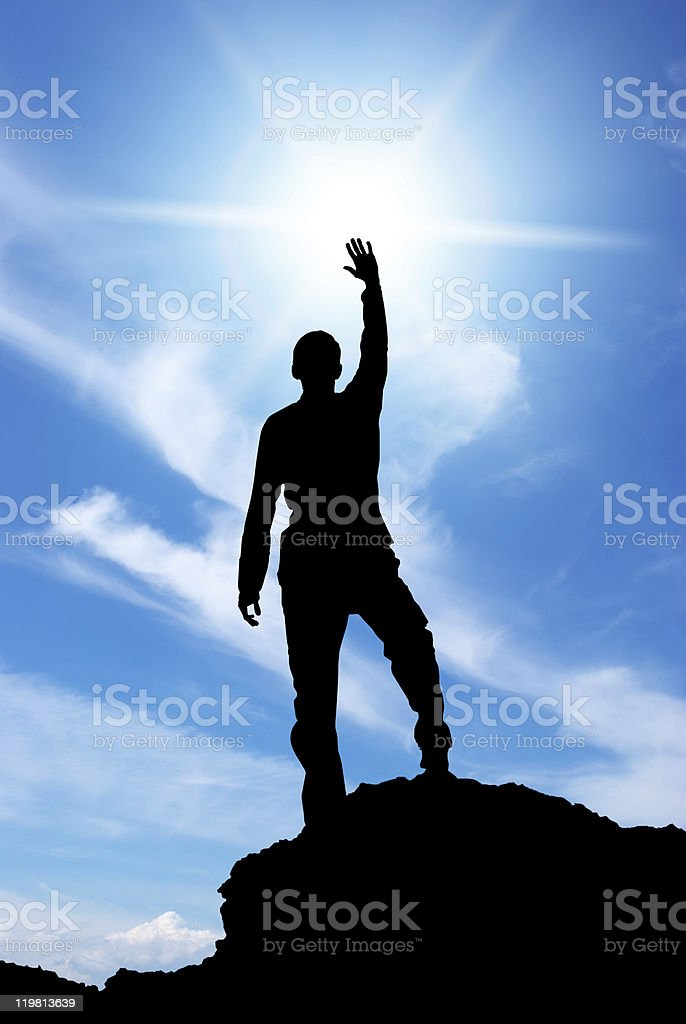 Silhouette of a man on top of a mountain reaching for sky royalty-free stock photo