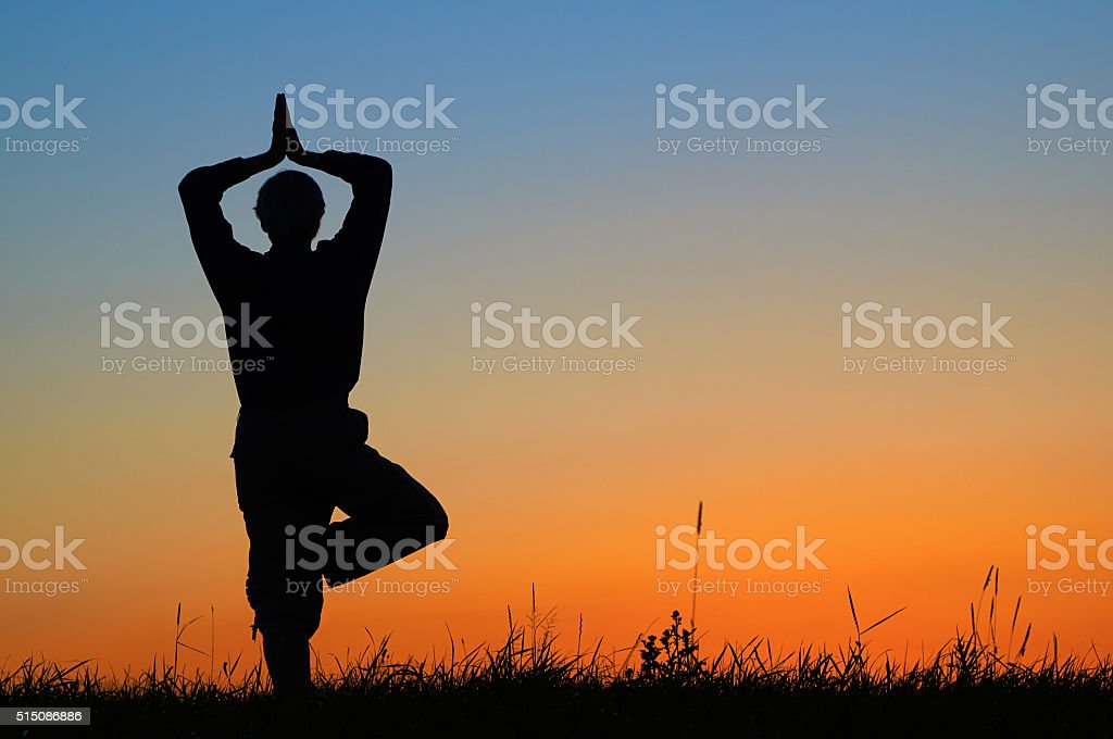Silhouette of a man practicing yoga in a position Vrikshasana stock photo