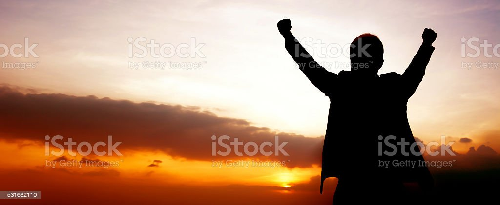 Silhouette of a man raising his arms stock photo