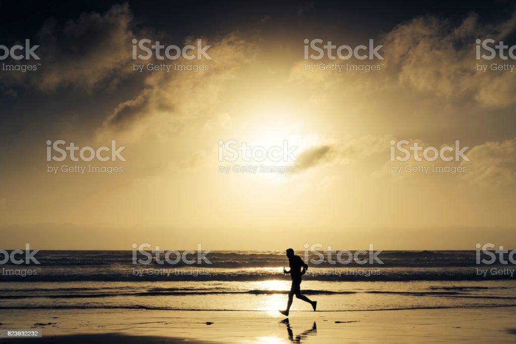 Silhouette of a Man Running along a Beach near Sunset. stock photo