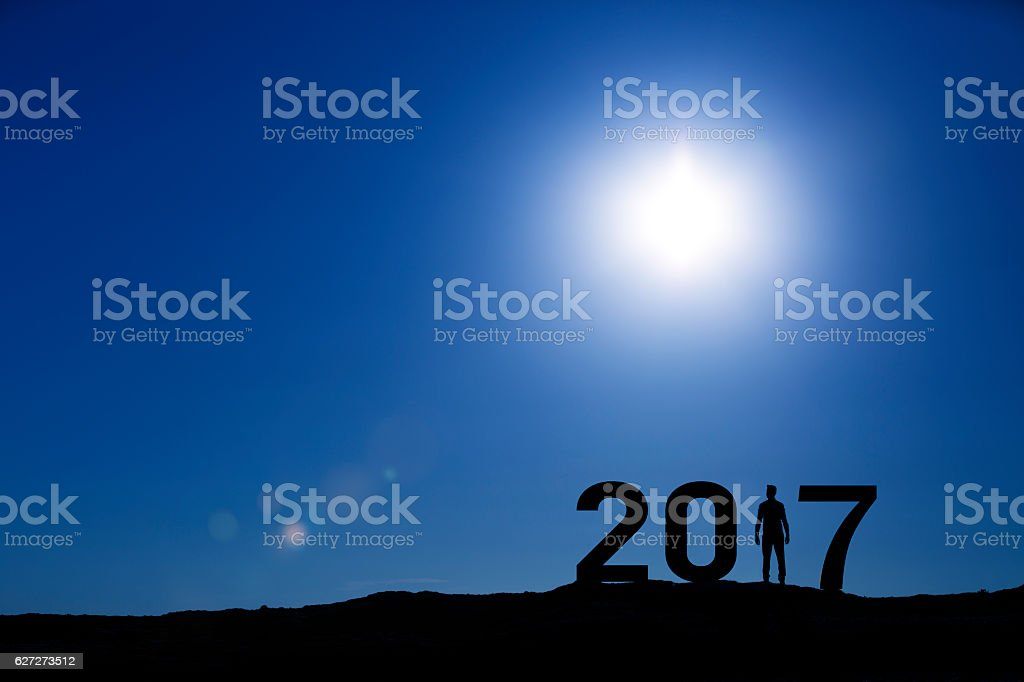 2017, silhouette of a man standing in the sun stock photo