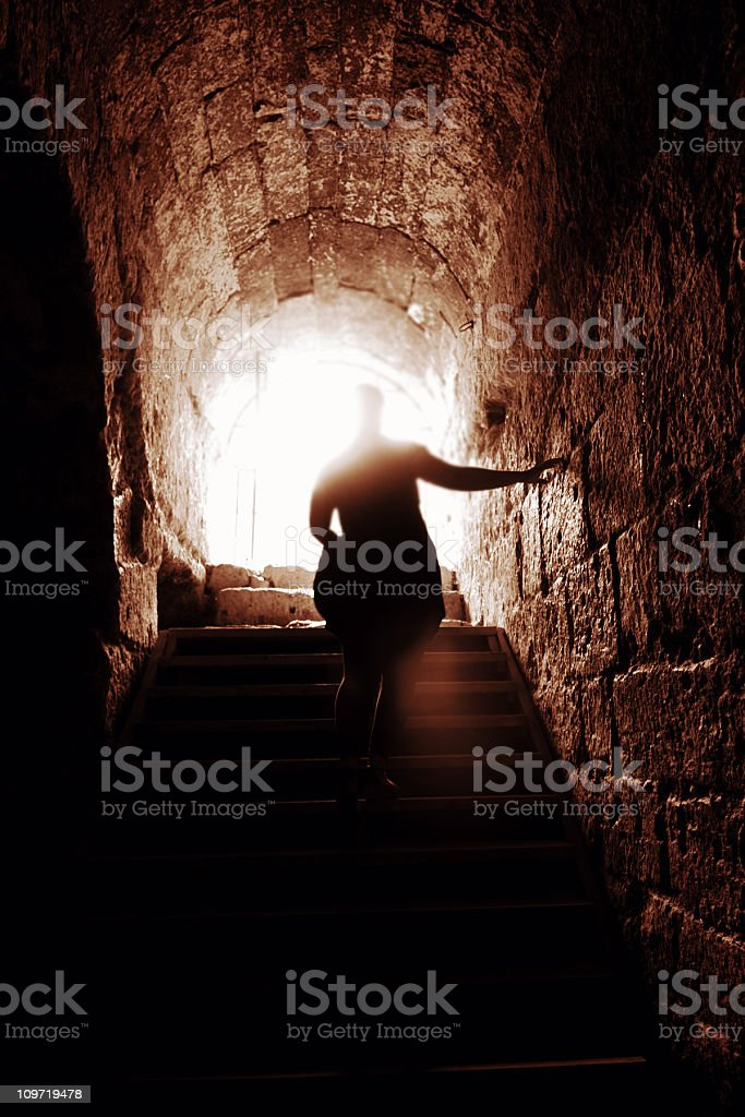 Silhouette of a man walking up stone steps of a tunnel royalty-free stock photo
