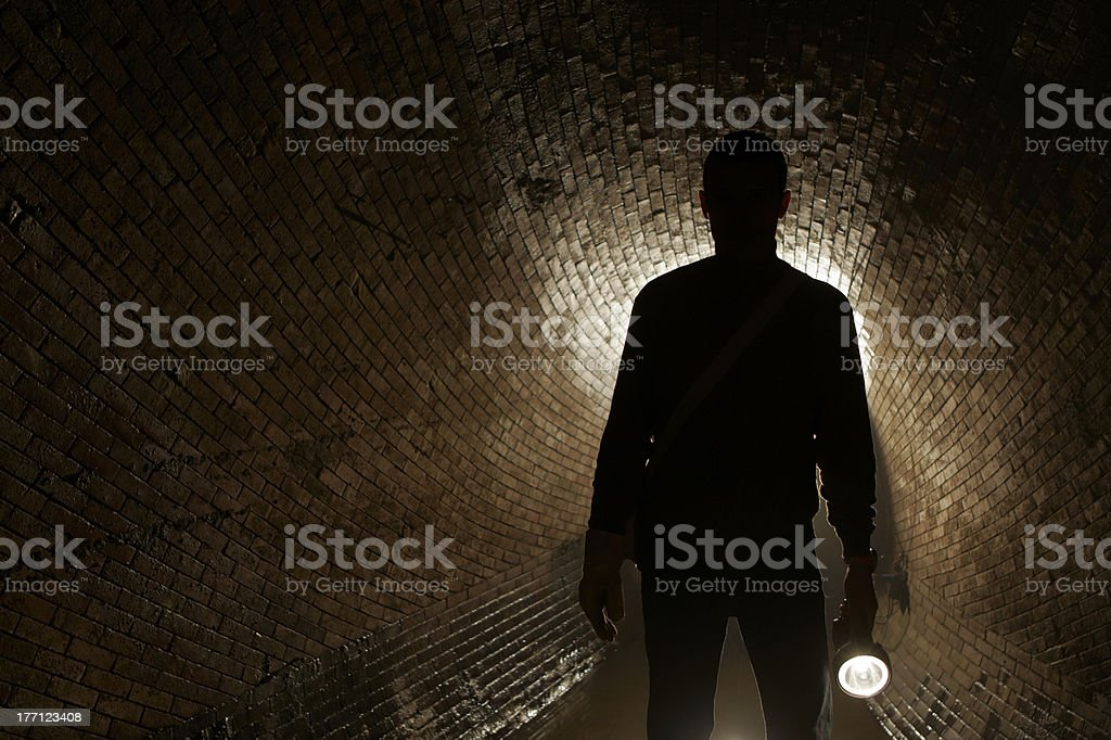 Silhouette of a man with a flashlight on a dark tunnel royalty-free stock photo