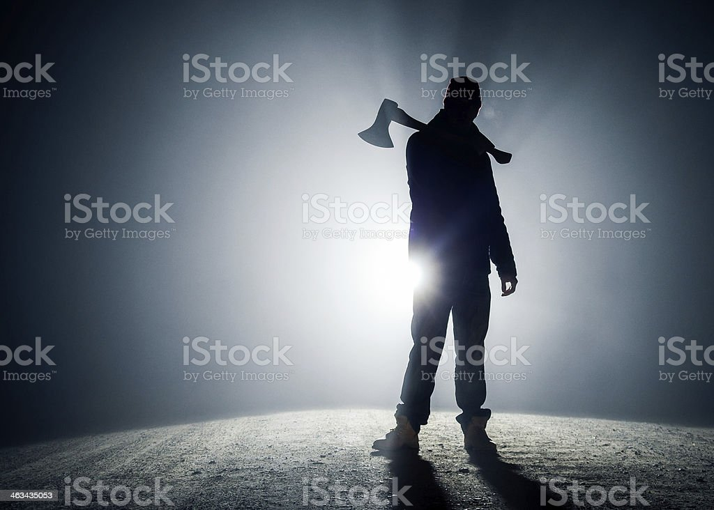 Silhouette of a man with an axe over his shoulder on road stock photo