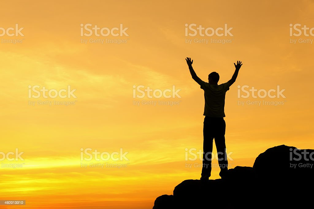 Silhouette of a man with raised-up arms at the sunset stock photo