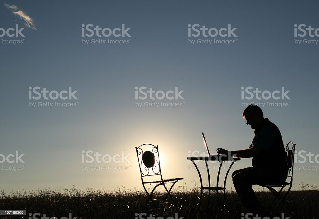 Silhouette of a Man Working Late Outside stock photo