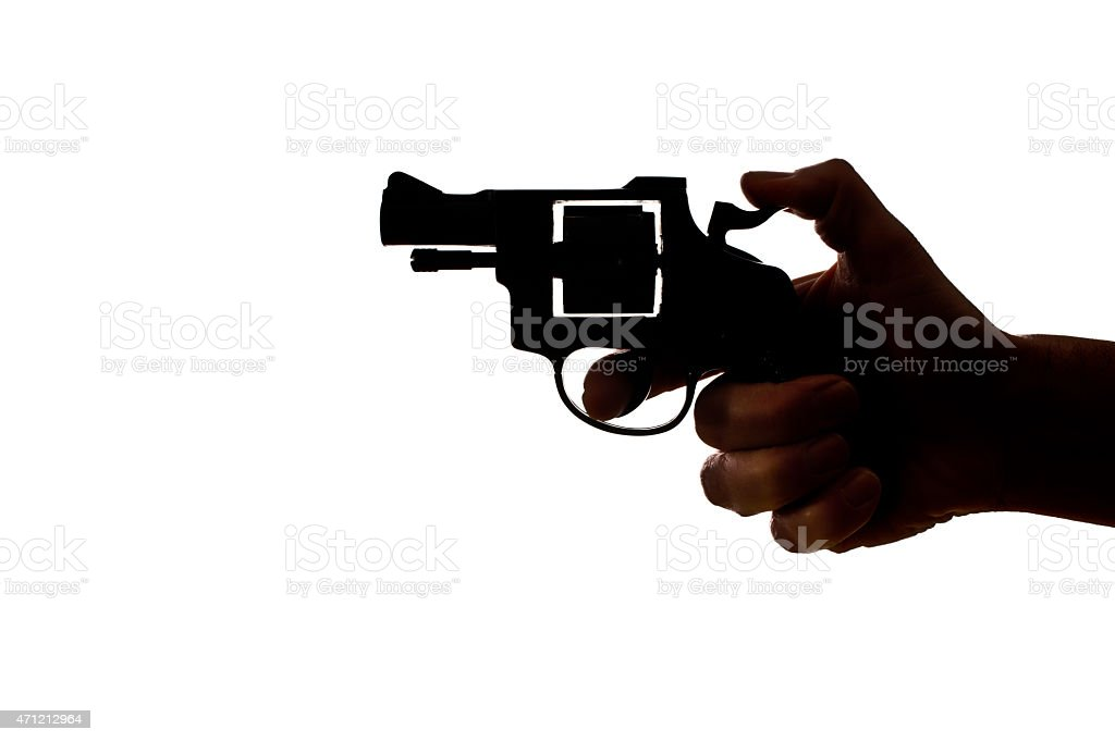 Silhouette of a mans hand with a handgun stock photo