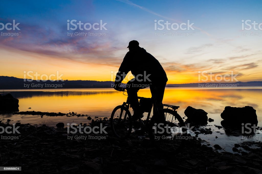 Silhouette of a mountain bike and cyclist at sunrise stock photo