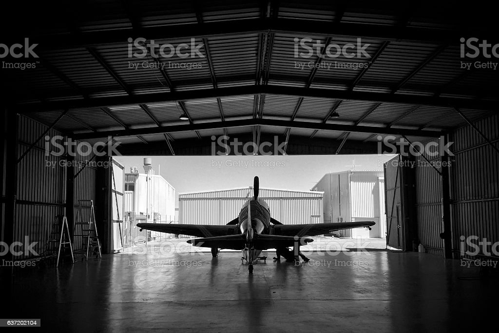 Silhouette of a P-51 Mustang fighter aircraft in a hangar stock photo